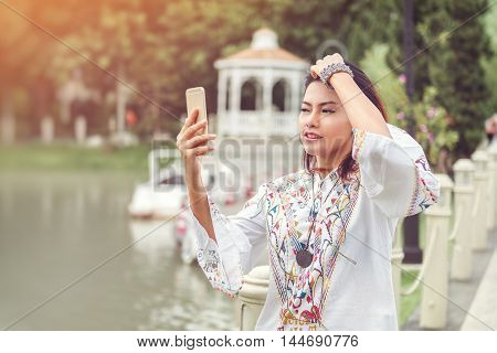 Photos of Asian woman looking at the phone and a smiley face relaxed moodFocus on face