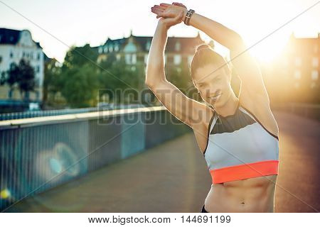 Female athlete smiles at camera and stretches by raising both arms overhead and leaning to one side