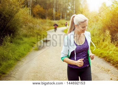 Happy and healthy girl runner on the road with other runners in distance