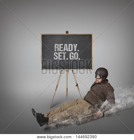 Ready Set Go text on blackboard with businessman sliding with a sledge