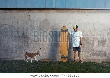 Longboarder With Basenji Dog Next To Gray Concrete Wall