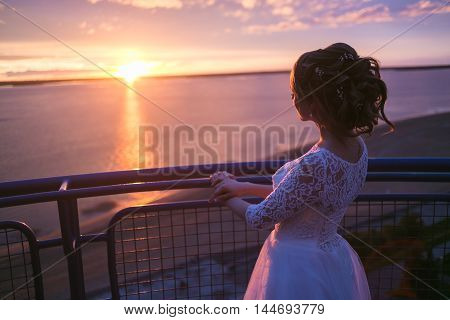 Beautiful women bride in a wedding dress with fluttering hair. Girl looking to colorful sunset on river.