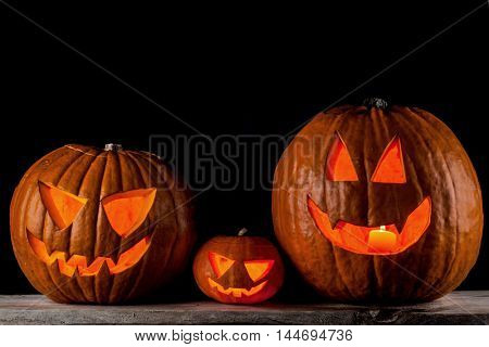 Thre Jack o lanterns halloween pumpkins on wooden table isolated on black background