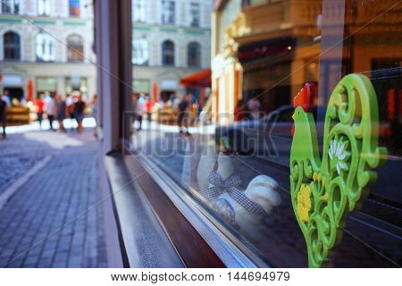 Green souvenir wooden cockerel with a red comb in a glass with reflection streets of Riga with tourists on a sunny day