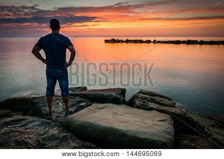Man looking to sunrise or sunset on ocean beach. Very long exposure photography