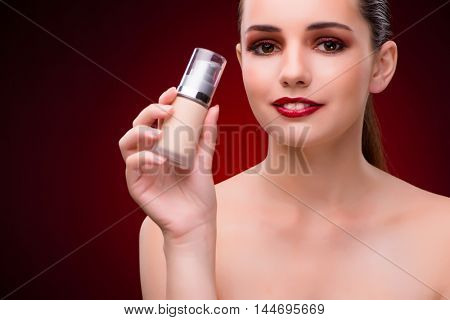 Woman with bottle of skincare cream
