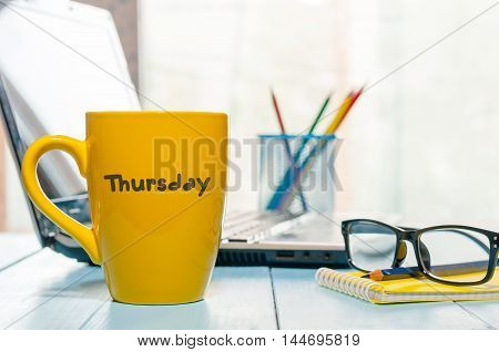 Thursday word written on yellow cup of coffee at maorning office workplace with laptop and glasses.