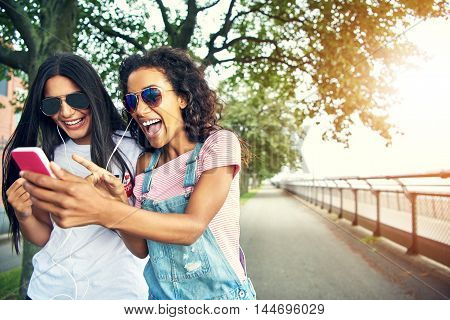 Friends holding mobile device pressing buttons laugh while standing on jogging path