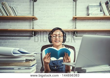 Picture of Asian women were happy to learn from reading and listeningFocus on face