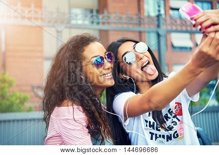 Two female friends on bench make silly faces while wearing sunglasses as they take a photo with their cell phone
