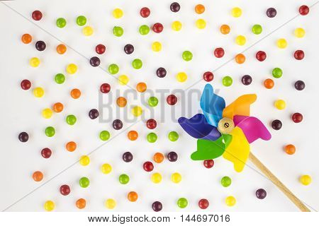 Colorful pinwheel and multicolored candies on white background. Flat lay. Top view