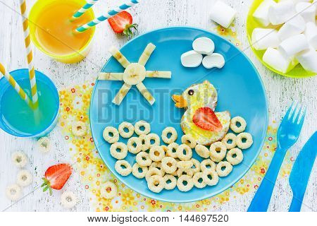 Funny idea for baby food - sandwich with sugar in the form of a duck swimming in the dry cereal rings top view