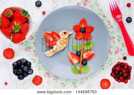 Fun food art idea for kids meal from fresh fruits and berries top view