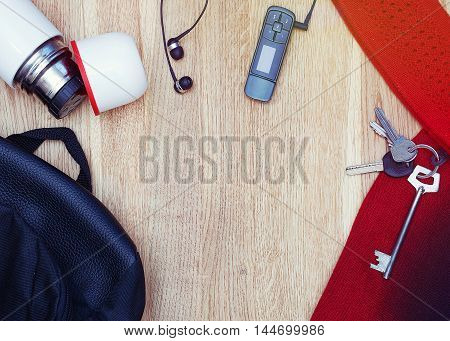 Overhead of essentials for modern young person. Different objects on wooden background: backpack thermos earphones music player keys scarf