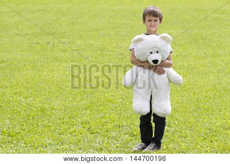 Little boy with teddy bear is looking at the camera. Outdoor summer day green grass background. Copy space for text