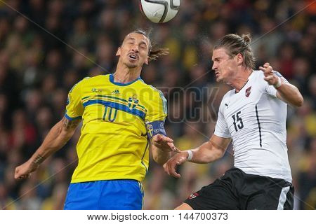 STOCKHOLM, SWEDEN - SEPTEMBER 8, 2015: Zlatan Ibrahimovic (Sweden) and Sebastian Proedl (Austria) fight for the ball in an European Championship qualification game.