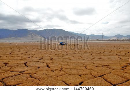 Long shot of a half buried blue car in very dry ground in the background are hills with a cloudy sky close to Chañaral in Chile, South America
