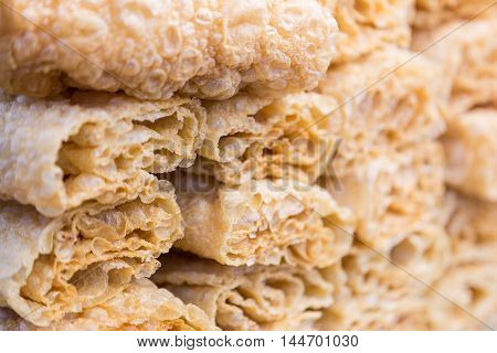 Close up of stacks of roll up fried tofu skins or bean curd selective focus with shallow depth of field showing texture of fried tofu skin