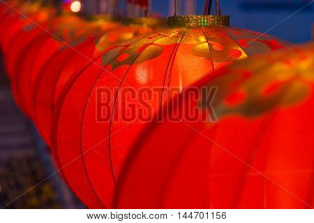 Row of red Chinese lanterns selective focus with blur foreground and background lanterns