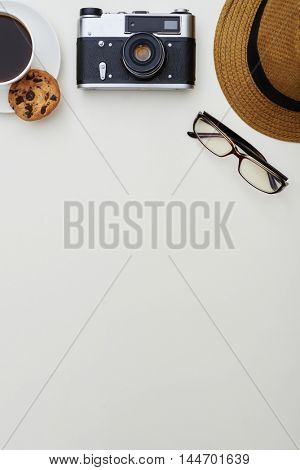 Top view of white surface with hat, eyeglasses, photo camera and a cup of coffee with cookie put on the upper part of it