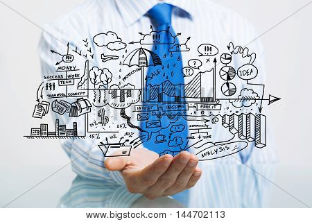Businessman at table presenting business sketched plan in palm