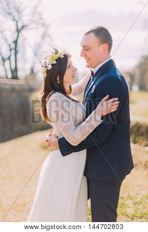 Close-up of happy stylish newlywed bride and groom hugging outdoor.