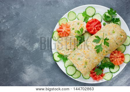 Festive rabbit minced roll with green peas and carrot on a plate with fresh tomatoes cucumbers and parsley. Dietary menu. Proper nutrition. Top view blank space for text