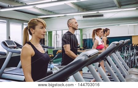 Group of people training over a treadmills on fitness center