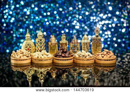 Eid and Ramadan Theme background with lanterns, perfumes and nuts against a blue glitter background