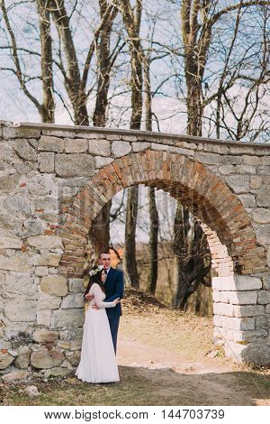 Newlywed pair pose at old ruined gate of ancient baroque castle wall.