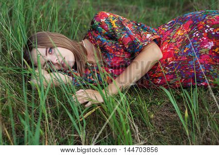 Young beautiful woman in a red dress laying on the grass