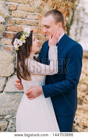 Newlywed couple pose near old ruined baroque castle wall.