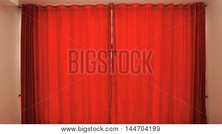 Window of hotel room with red curtains closed background