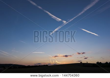 The sunset and white condensation trails (line-shaped clouds) on sky in summer