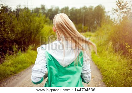 Happy and healthy girl runner on the road