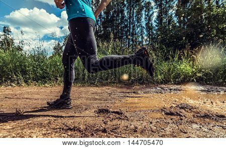 Athlete running through the dirty puddle in the rural road