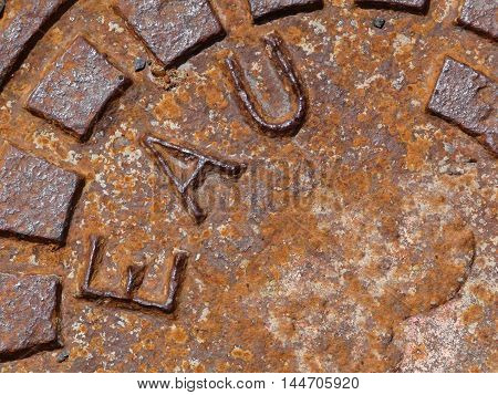 Closeup of a rusted water manhole cover