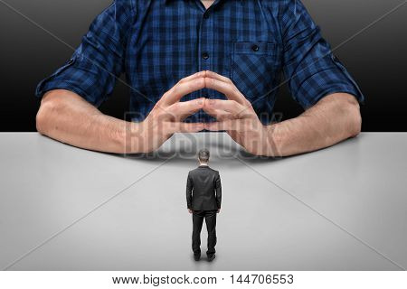 Businessman stands in front of a cropped portrait of a big man sitting with his fingers clasped. Business staff. Boss and employee. Implicit obedience. Guilt and humiliation.
