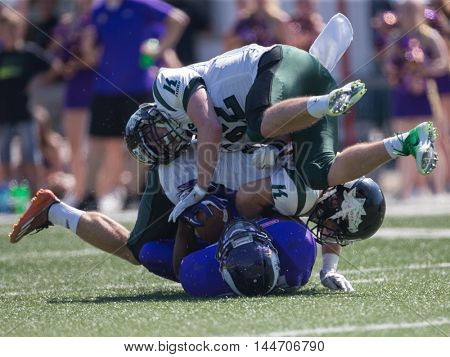 VIENNA, AUSTRIA - JULY 10, 2016: Thomas Meznik (Danube Dragons) tackles Tutanch Stevenson-Anthony-Maw (Vienna Vikings) in a game of the Austrian Football League.