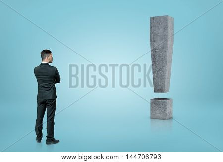 Back view of a businessman looking at big 3D concrete exclamation mark isolated on blue background. Ideas and concepts. Business staff. Solving problems.