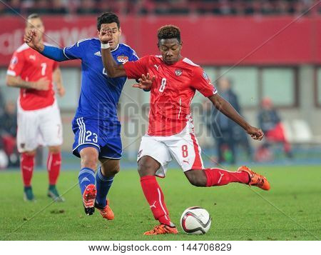 VIENNA, AUSTRIA - OCTOBER 12, 2015: Michele Polverino (Liechtenstein) and David Alaba (Austria) fight for the ball in an European Championship qualification game.