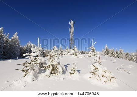 telecommunications tower and snow wrapped trees in Sumava Czech republic