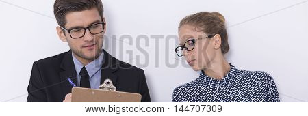 Young woman looking ath the notes of her friend sitting close to her