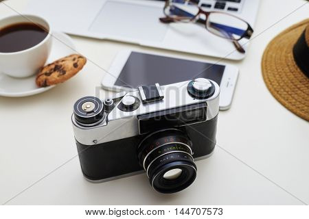 Camera in focus on the foreground and gadgets, eyeglasses, hat and a cup of coffee with cookie in blur on the background on white table