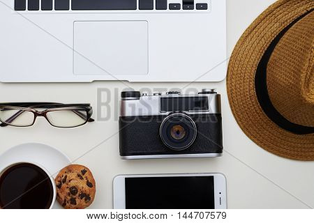 Top view of white table with photo camera in the middle and frame of laptop, eyeglasses, hat, phone and a cup of coffee with cookie