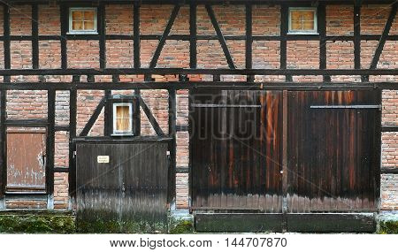 Wall of the old half-timbered buildings of red brick with a wooden frame and door gates. Waiblingen Germany.