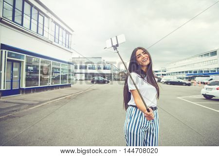 Happy woman with long hair and striped blue and white pants taking a self portrait using a smart phone attached to a long pole known as selfie stick in the middle of street