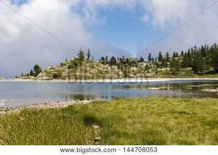 Alpine landscape with lake mountains and fir trees