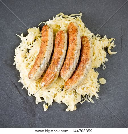 grilled sausages and cabbage on black plate