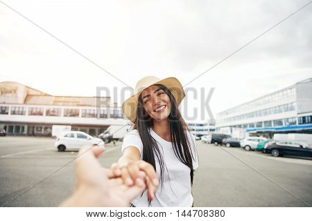 Woman standing in parking lot reaches out toward camera and smiles while wearing a straw hat